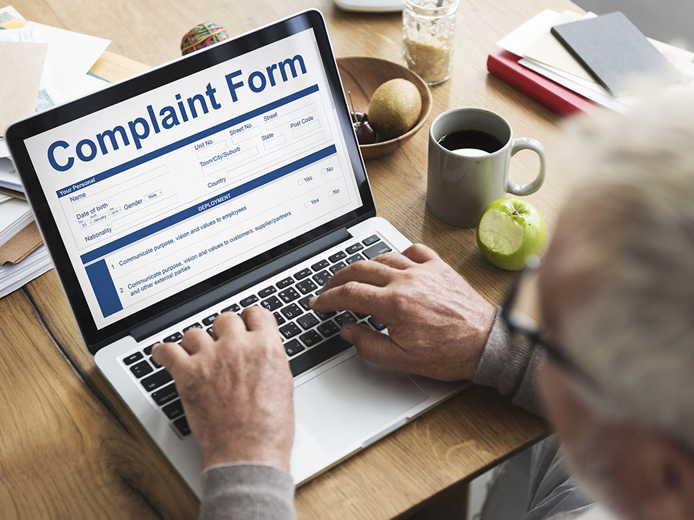a consumer is filling a complaint form on his computer