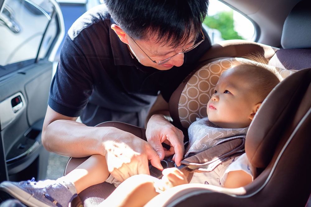a dad is securing his baby in the carseat for safety