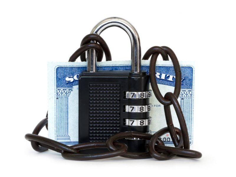 Lock and chains around a social security card.