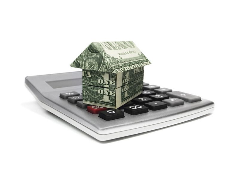 Origami house made of dollar bills, on a calculator.