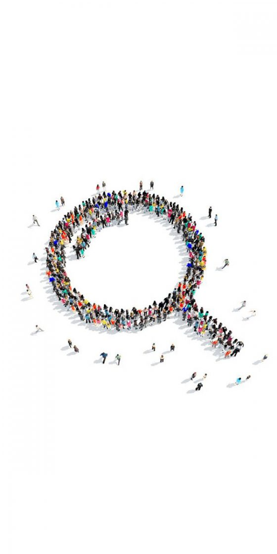 Many people grouped together in a magnifying glass formation.