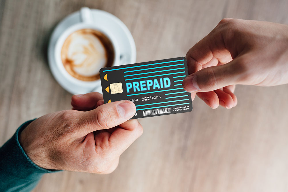 a consumer is paying for his coffee with a prepaid card