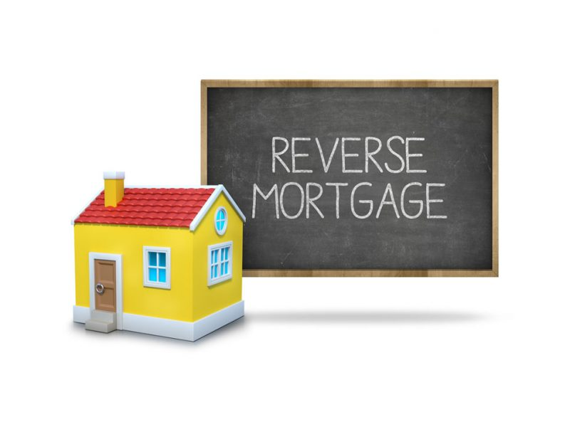 a picture of a house with a blackboard with reverse mortgage written on it