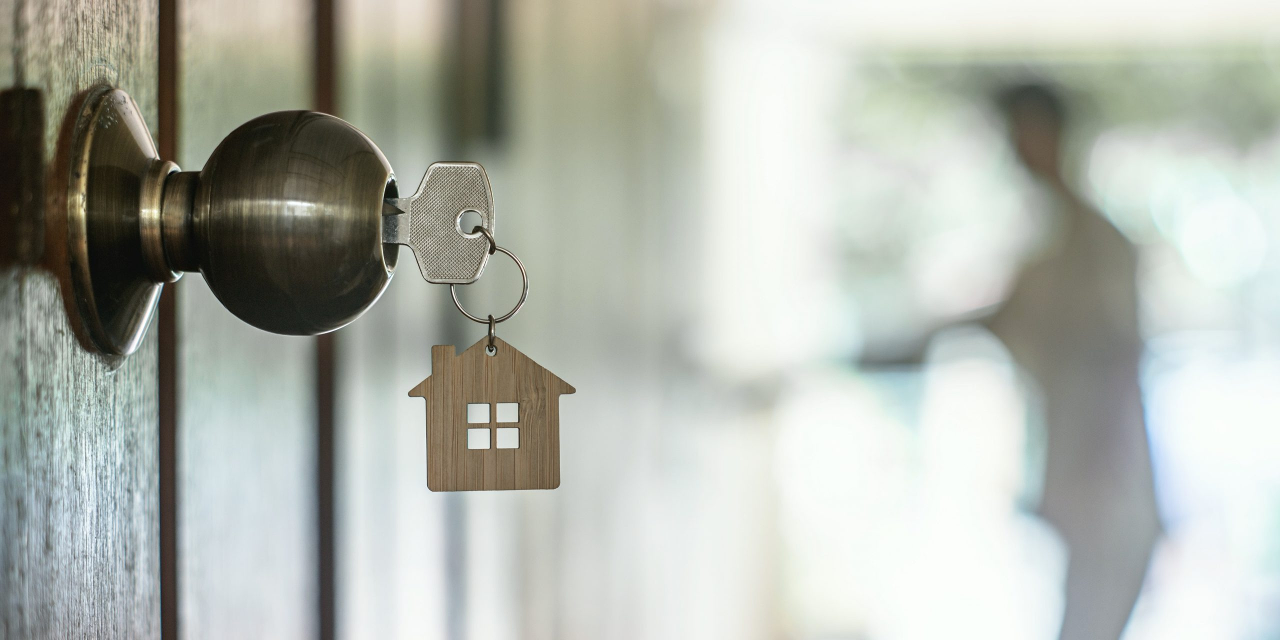 Keys to a home with a house-shaped keychain