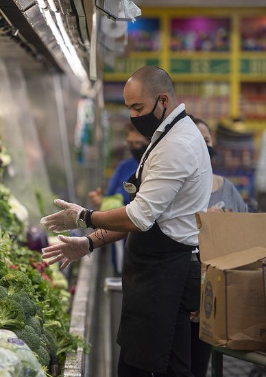 Grocery store produce worker stacks veggies