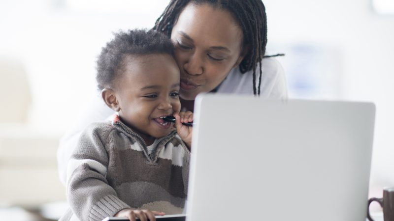 A mother holding her child with the laptop open on the table