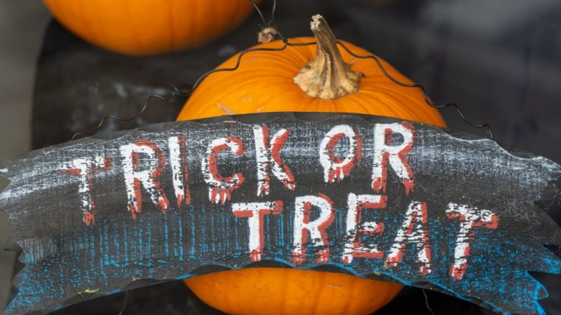 """Pumpkins on a staircase with a wooden sign with the words """"Trick or Treat"""""""